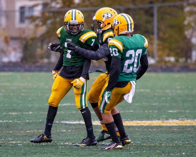 Delwuan Gaston (7) of Farmington Hills Harrison celebrates a sack in the second half against Cranbrook Kingswood with teammates Michael Alford (5) and Xavier Goldsmith (20). Harrison won its predistrict game on Saturday.