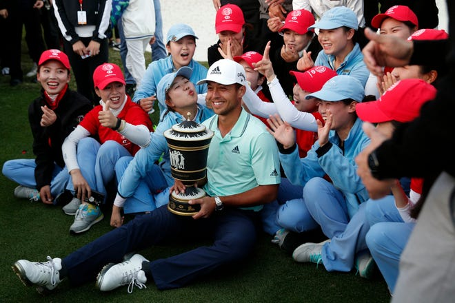 Xander Schauffele poses with the trophy near the golf course staff after winning the HSBC Champions at the Sheshan International Golf Club in Shanghai on Sunday.