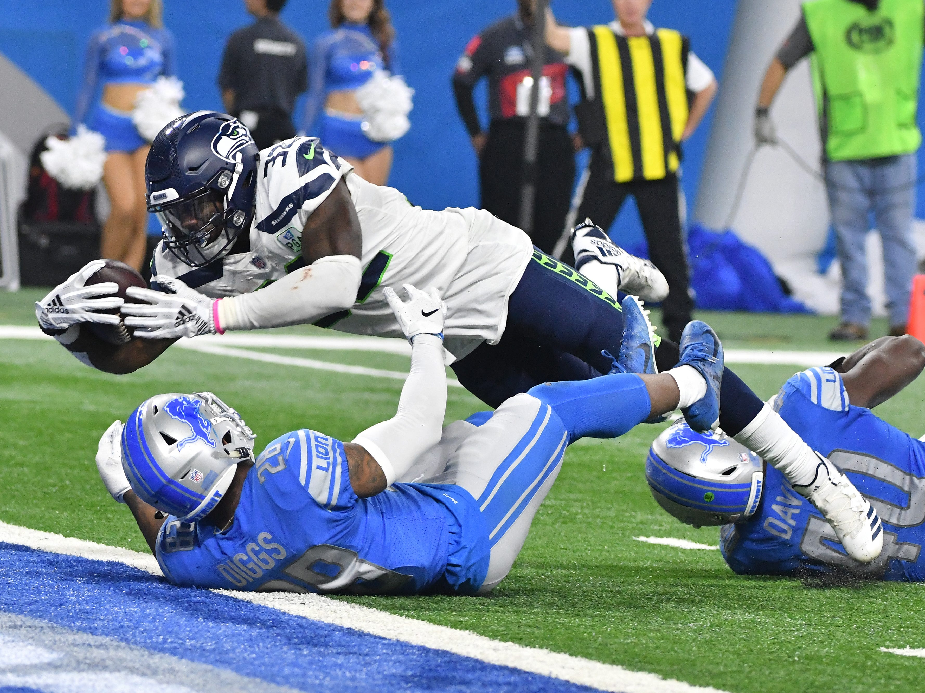 Seattle running back Chris Carson drives through and over Lions defense of Quandre Diggs and Jarrad Davis into the end zone for a touchdown in the fourth quarter.