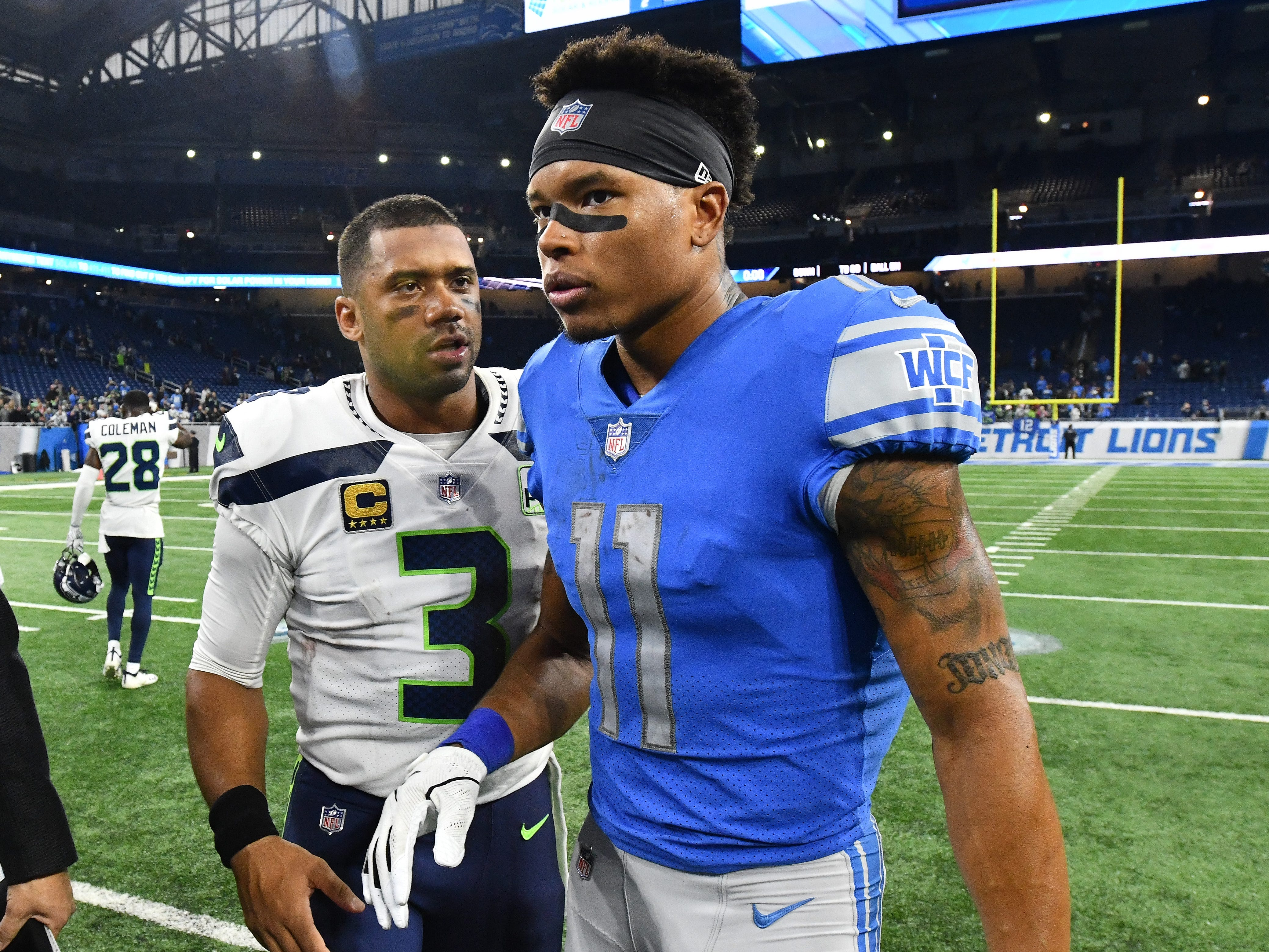 Seahawks quarterback Russell Wilson and Lions' Marvin Jones Jr. chat on the field after the 28-14 Seattle victory over Detroit.
