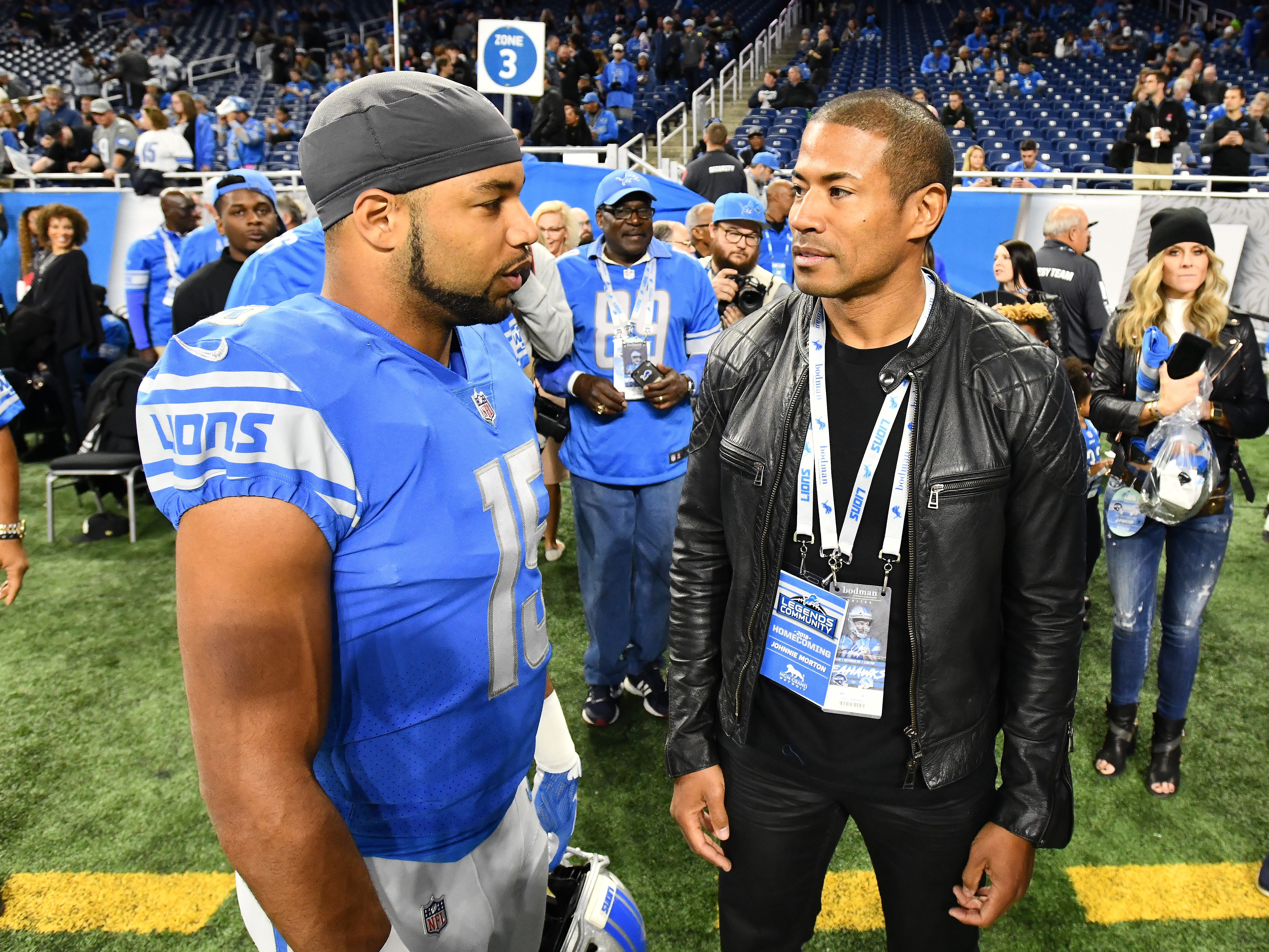 Lions wide receiver Golden Tate and former Lions wide receiver Johnny Morton talk on the field before the game.