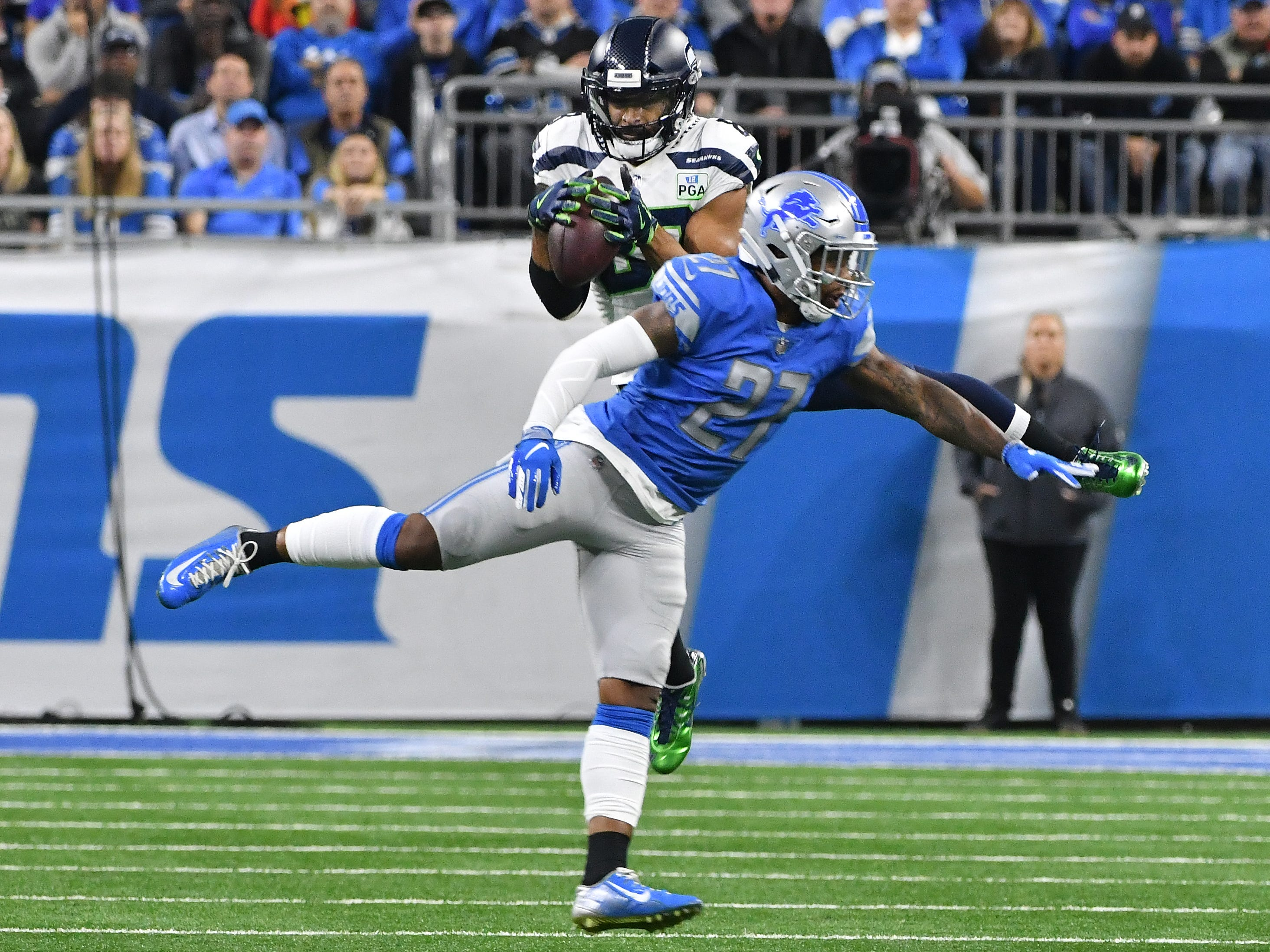 Seahawks' Doug Baldwin pulls in a reception with Lions' Glover Quin defending in the second quarter.