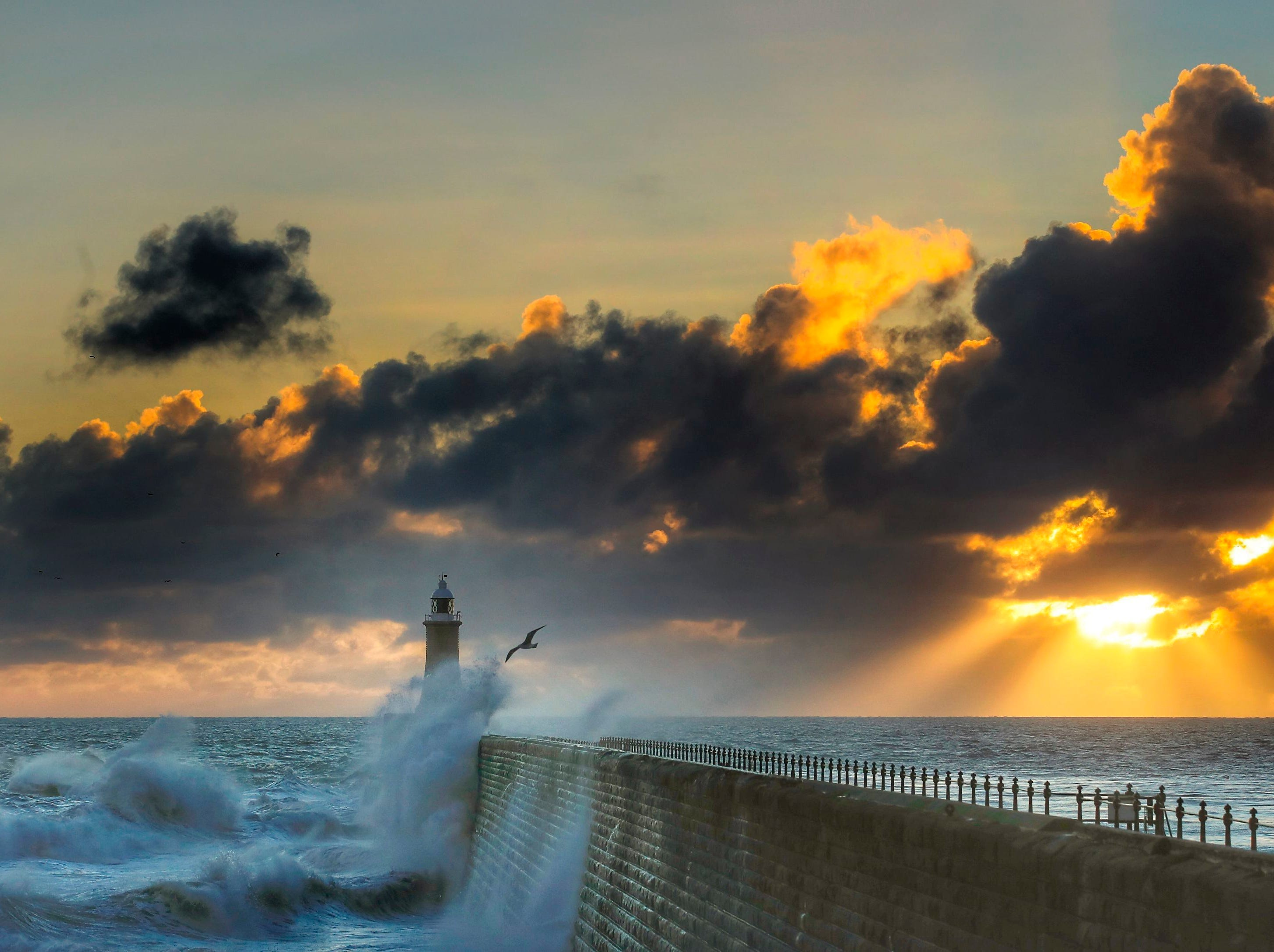 Rough seas are buffeted against Tynemouth Pier as the sun rises in Tynemouth, England, Sunday, Oct. 28, 2018.