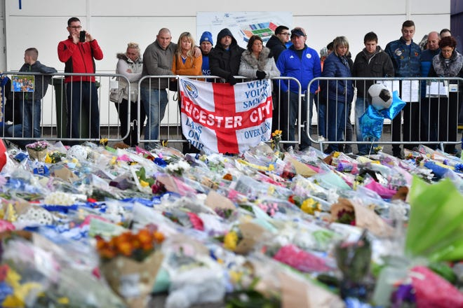 Supporters pause at the pile of floral tributes outside Leicester City Football Club's King Power Stadium in Leicester, eastern England, on Sunday.