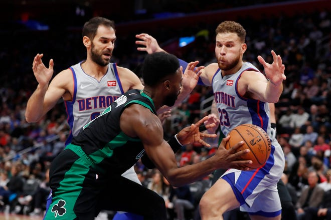 Boston Celtics guard Jaylen Brown passes as Detroit Pistons guard Jose Calderon, left, and forward Blake Griffin defend during the first half.