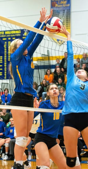 Oconto's Baleigh Gering blocks a tip attempt from Rosie Butler of St. Mary's Catholic in the sectional semifinal on Oct. 26.