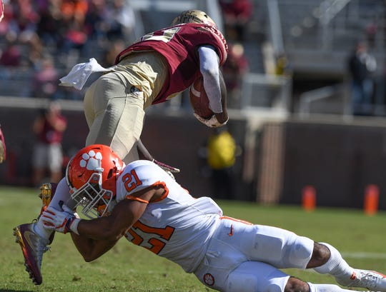 Clemson running back Darien Rencher (21) tries to bring down Florida State running back Anthony Grant (10) during the 4th quarter at Florida State's Doak Campbell Stadium in Tallahassee, Fl, Saturday, October 27, 2018