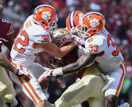 Clemson safety Kyle Cote (32), left, and linebacker J.D. Davis (33) bring down Florida State running back Anthony Grant (10) during the 1st quarter Saturday, October 27, 2018 at Florida State's Doak Campbell Stadium in Tallahassee, Fl.
