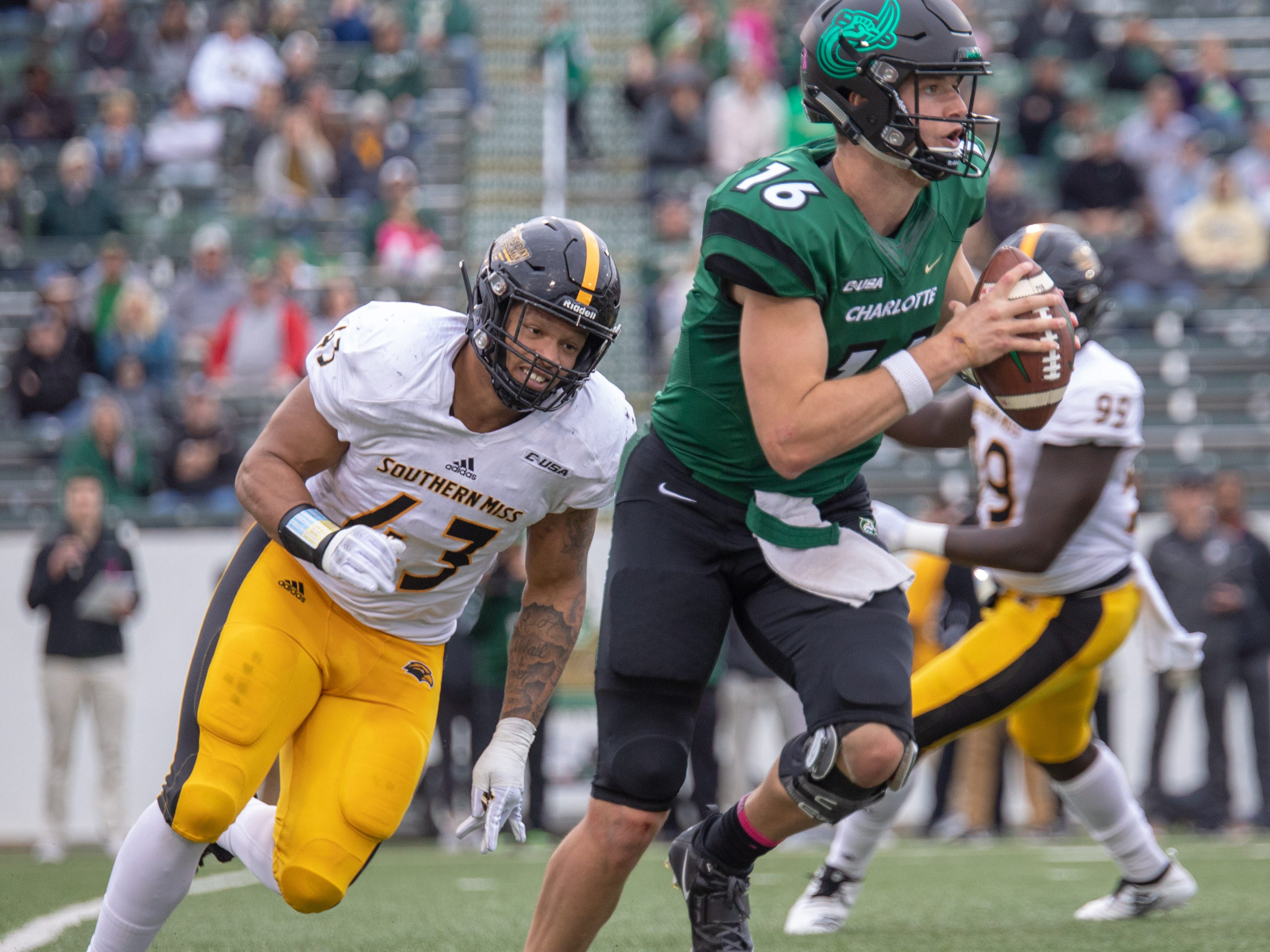 Charlotte quarterback Evan Shirreffs rolls out looking for a receiver as Southern Miss linebacker Seth Holloway (43) gives chase Saturday at Charlotte, N.C.