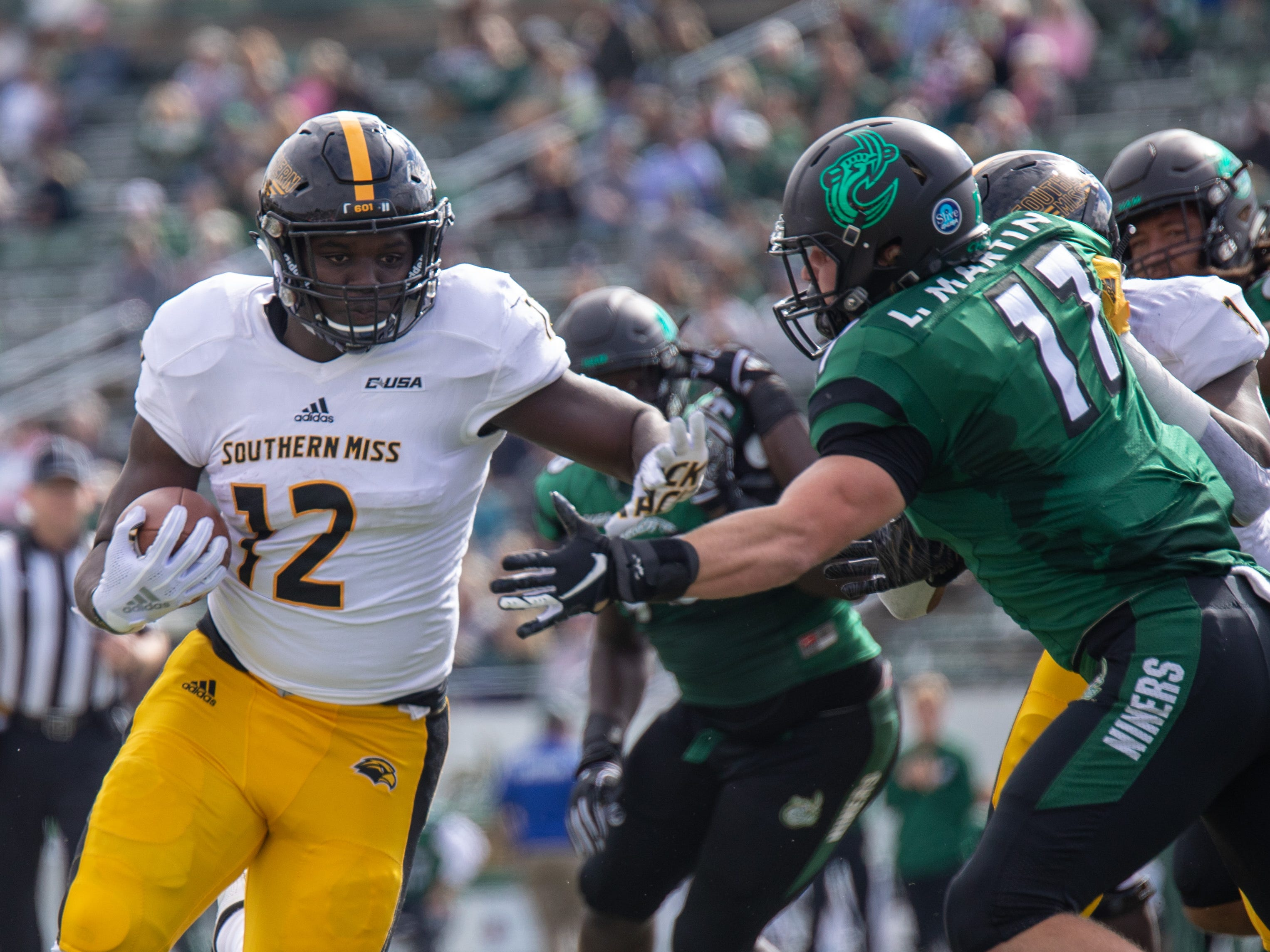 Southern Miss tailback Steven Anderson (12) tries to hit the corner as Charlotte defender Luke Martin (17) tries to make the tackle Saturday in Charlotte, N.C.