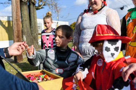 Children receive candy from community members during the Halloween Trunk or Treat Extravaganza along a blocked off route on Powell and Alvasia Streets in Henderson, Ky., Saturday, Oct. 27, 2018.