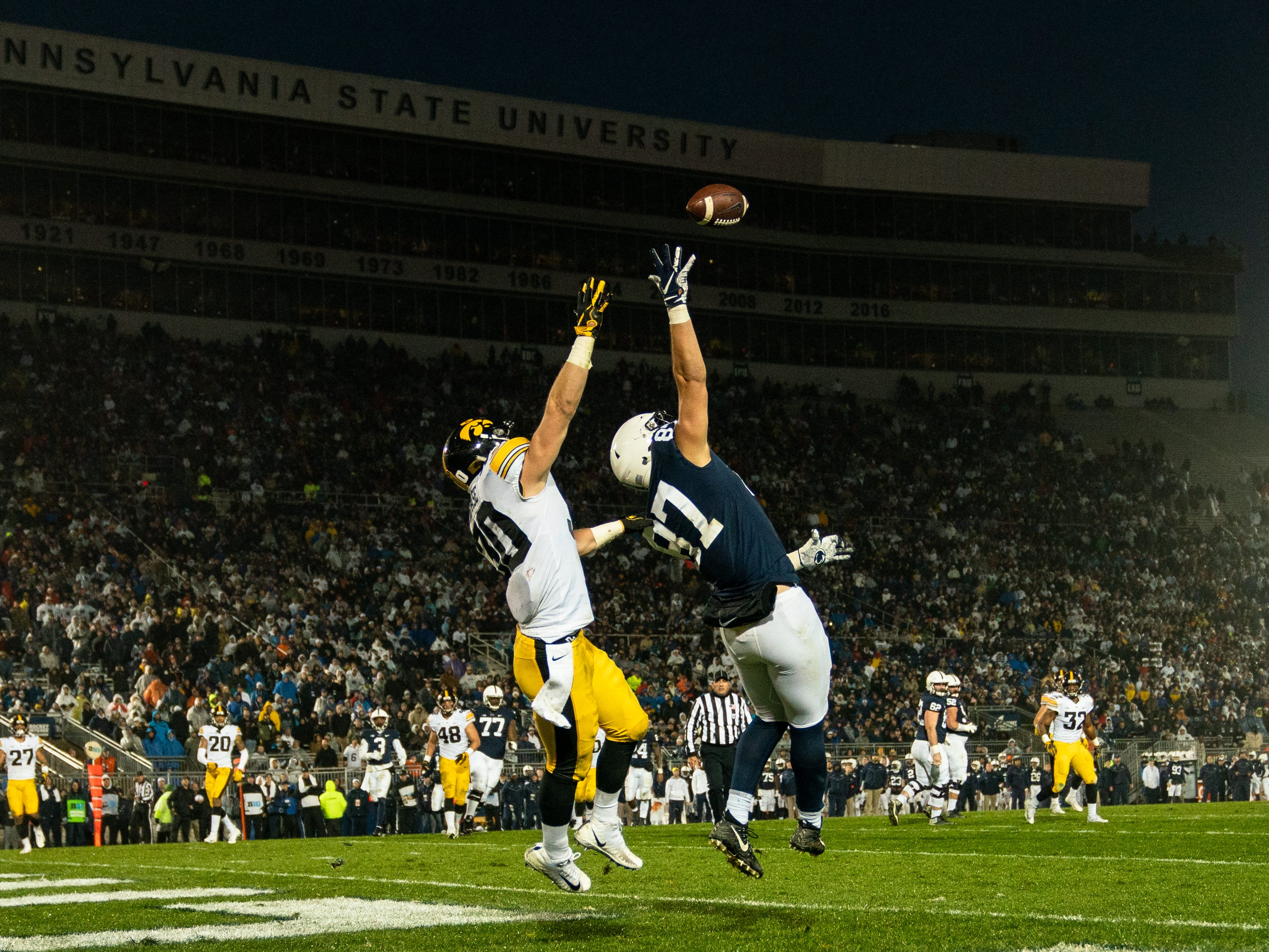 Pat Freiermuth #87 of the Penn State Nittany Lions and Jake Gervase #30 of the Iowa Hawkeyes go up for a pass during a game at Beaver Stadium on Saturday, October 27, 2018, in State College, Pennsylvania.