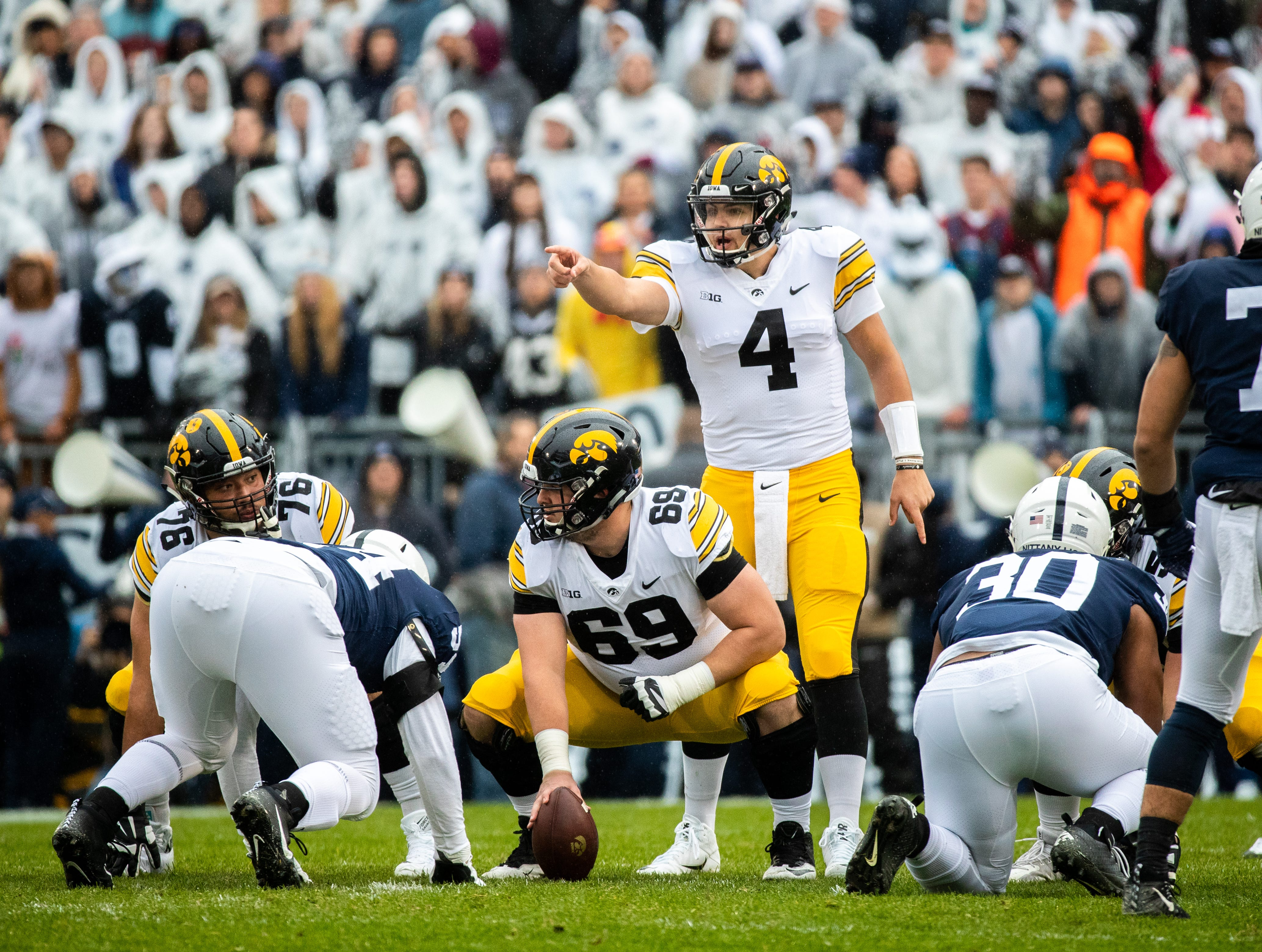 Nate Stanley #4 of the Iowa Hawkeyes before taking the snap from Keegan Render #69 of the Iowa Hawkeyes during a game against the Penn State Nittany Lions at of Beaver Stadium on Saturday, October 27, 2018, in State College, Pennsylvania.outside of Beaver Stadium on Saturday, October 27, 2018, in State College, Pennsylvania.