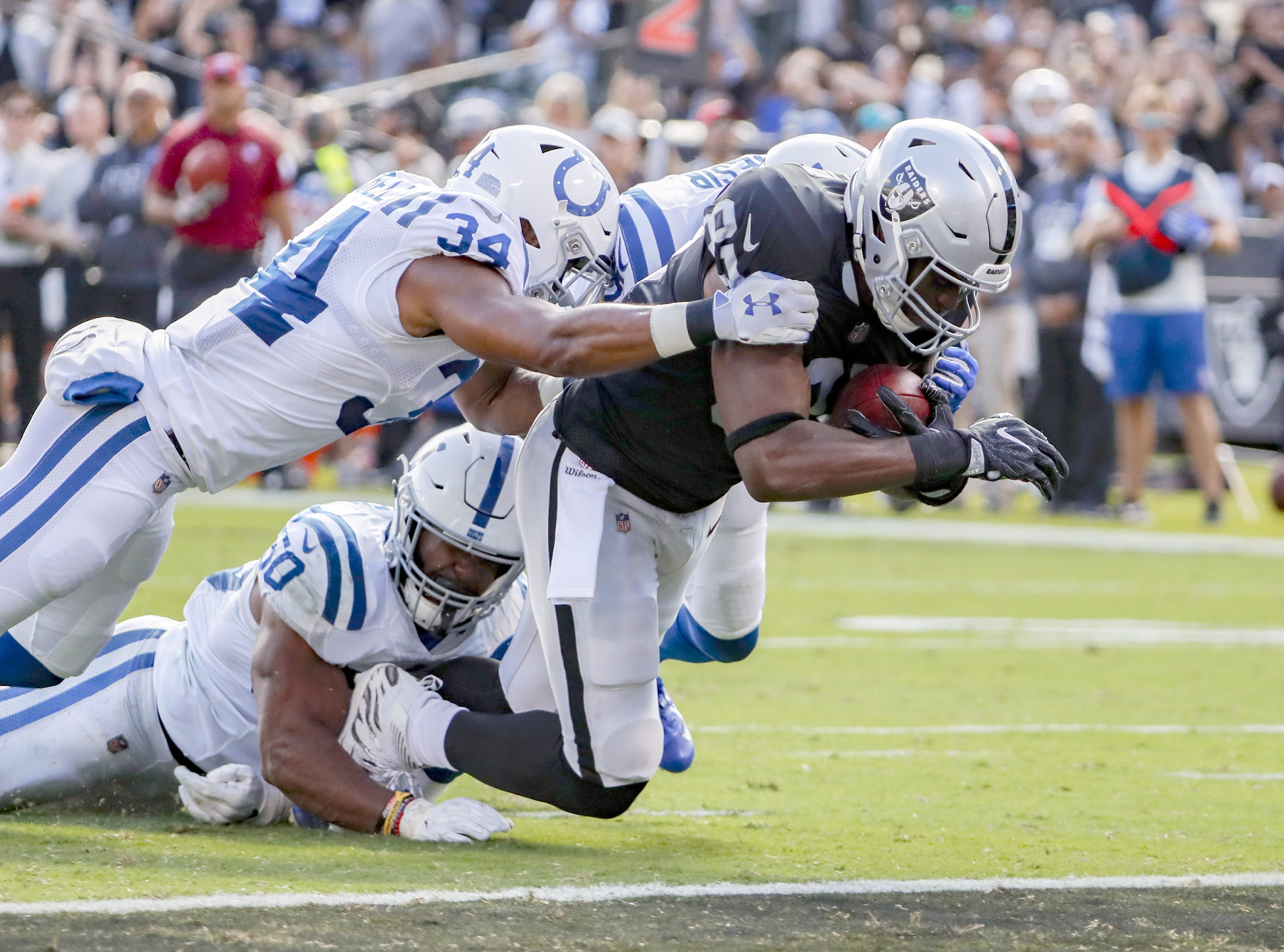 Oakland Raiders tight end Jared Cook (87) can't be stopped by Indianapolis Colts strong safety Mike Mitchell (34) and linebacker Anthony Walker (50) as he runs into the end zone to score during the first half of action. The Oakland Raiders hosted the Indianapolis Colts at The Coliseum in Oakland, California, Sunday, Oct. 28, 2018.