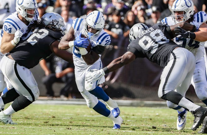 Indianapolis Colts running back Marlon Mack (25) rushes the ball into the Oakland Raider defense for an 8-yard gain.