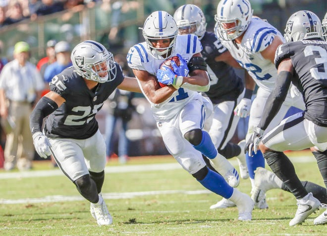 Indianapolis Colts running back Nyheim Hines (21) protects the ball as he rushes the ball through the Oakland Raider defense.
