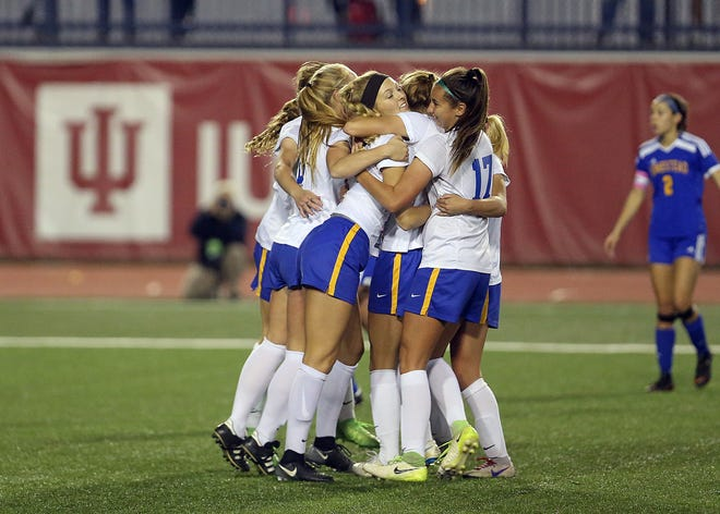 Carmel celebrates after Kelsie James (5) scores a goal in the first half of the IHSAA class 3A state final Saturday at IUPUI's Michael A. Carroll Stadium in Indianapolis. Carmel defeated Homestead 2-1 in overtime to take the state title.