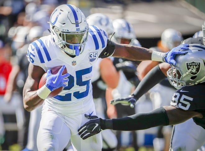 Indianapolis Colts running back Marlon Mack (25) fends off the tackle of Oakland Raiders defensive end Fadol Brown (95) as he rushes the ball up field during the first half of action. The Oakland Raiders hosted the Indianapolis Colts at The Coliseum in Oakland, California, Sunday, Oct. 28, 2018.