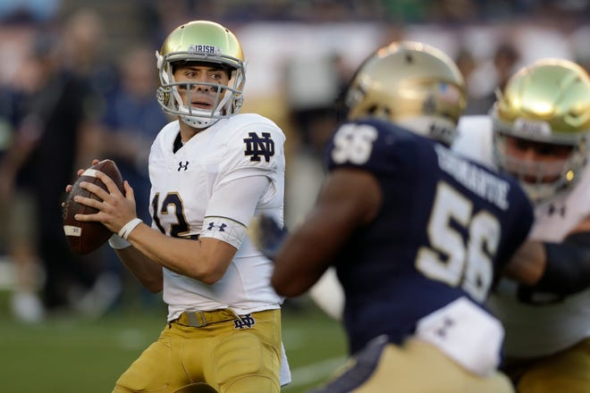 Notre Dame quarterback Ian Book looks to throw a pass against Navy on Saturday. His season completion percentage is now 76.5.  (AP Photo/Gregory Bull)