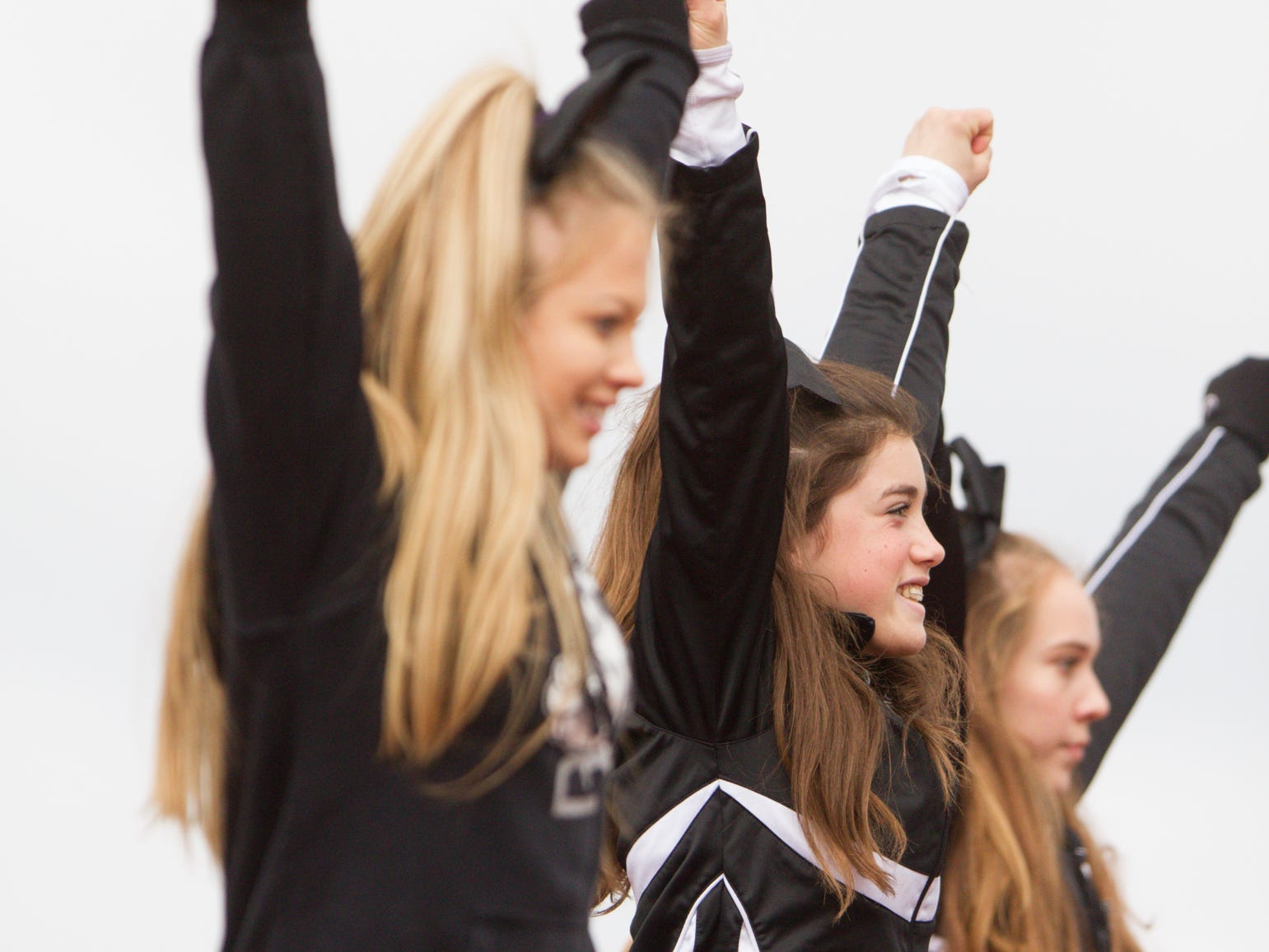 From left, Brighton cheerleaders Lexi Maximoff, Riley Harvill and Grace Anthony get the spirit going at the playoff game at East Kentwood Saturday, Oct. 27, 2018.