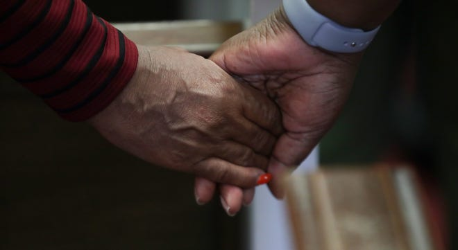 Members of the First Baptist Church of Jeffersontown in Kentucky hold hands during a Sunday morning prayer service Oct. 28, 2018.