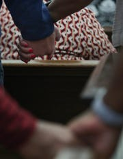Members of the First Baptist Church of Jeffersontown hold hands during a Sunday morning prayer. Oct. 28, 2018