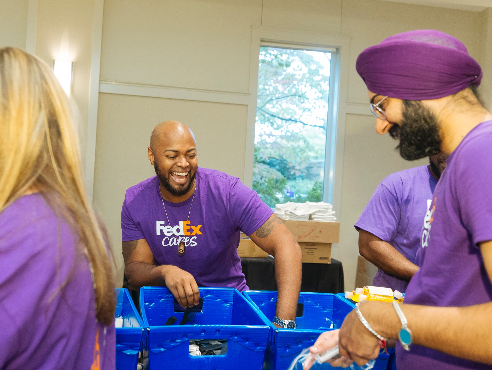 Jerome Heard sings along with fellow FedEx volunteers while assembling hygiene kits at the Memphis Botanic Gardens for  Hurricanes Florence and Michael relief.