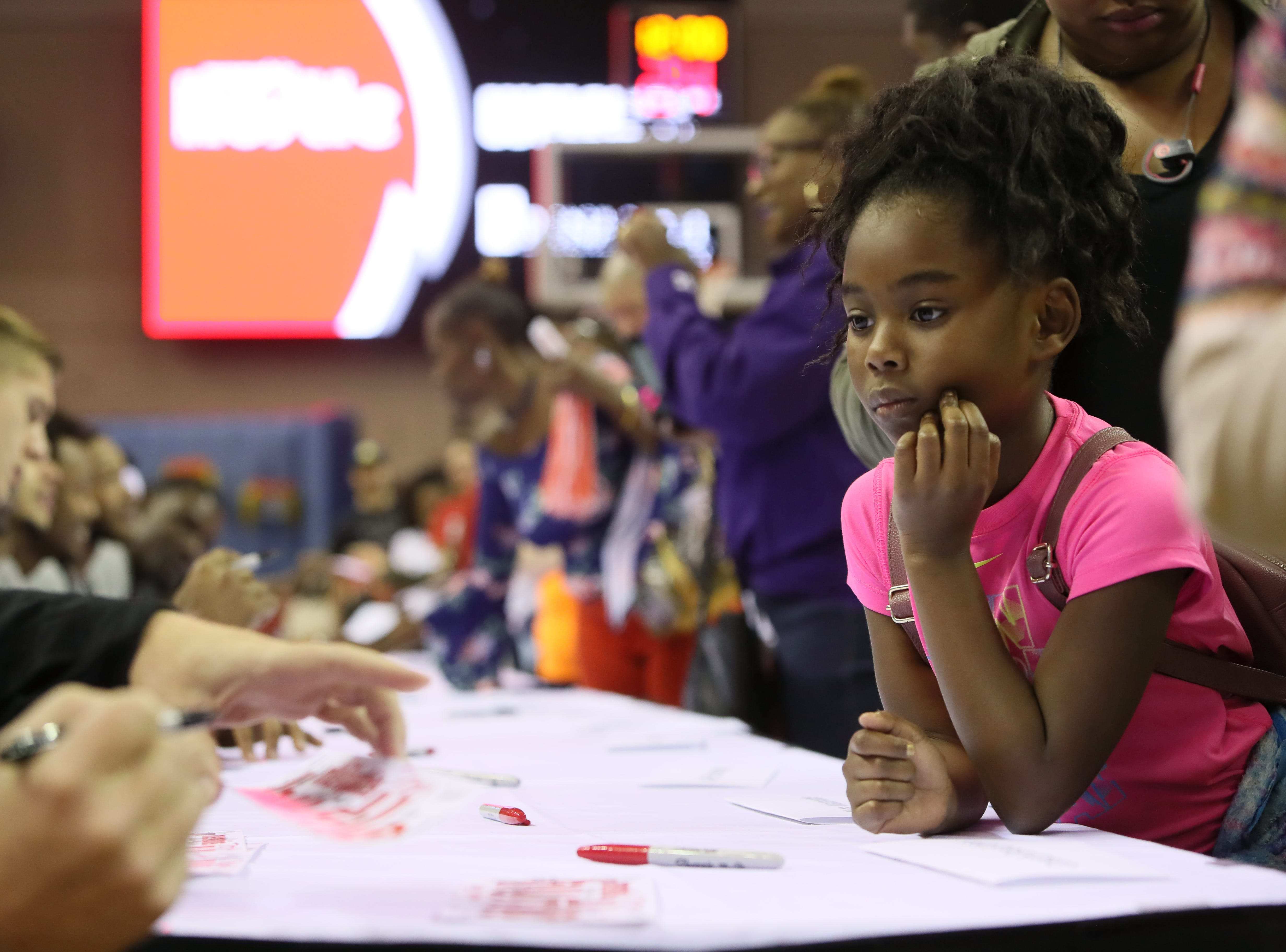 Azaria Dennis, 7, patiently waits for her autographs from players and coaches during the Memphis Hustle Family Fun Day at the Landers Center on Sunday, Oct. 28, 2018.