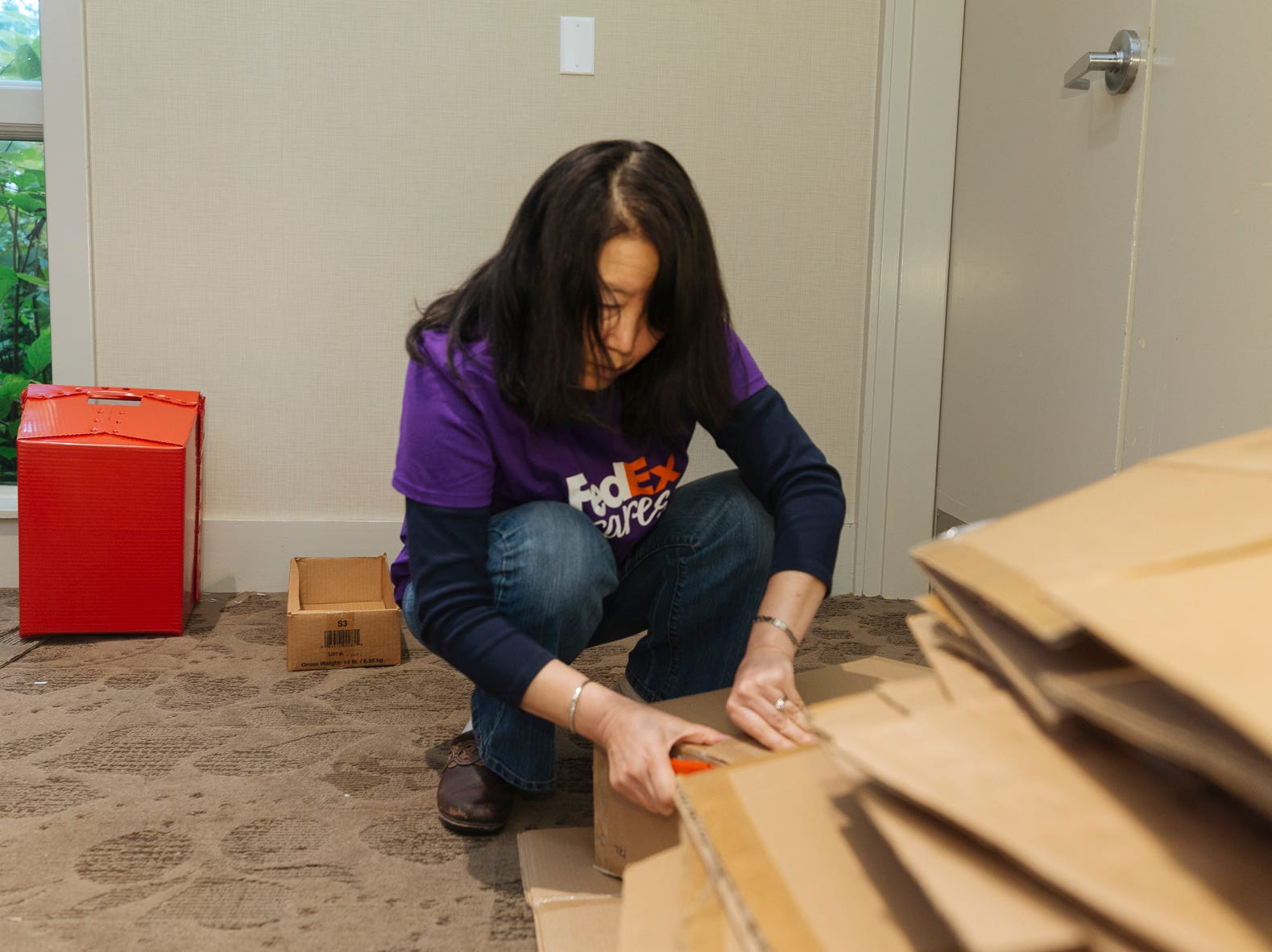 Fan Shen assembles box for fellow FedEx Cares volunteers preparing 3,600 hygiene kits for victims of Hurricanes Florence and Michael.