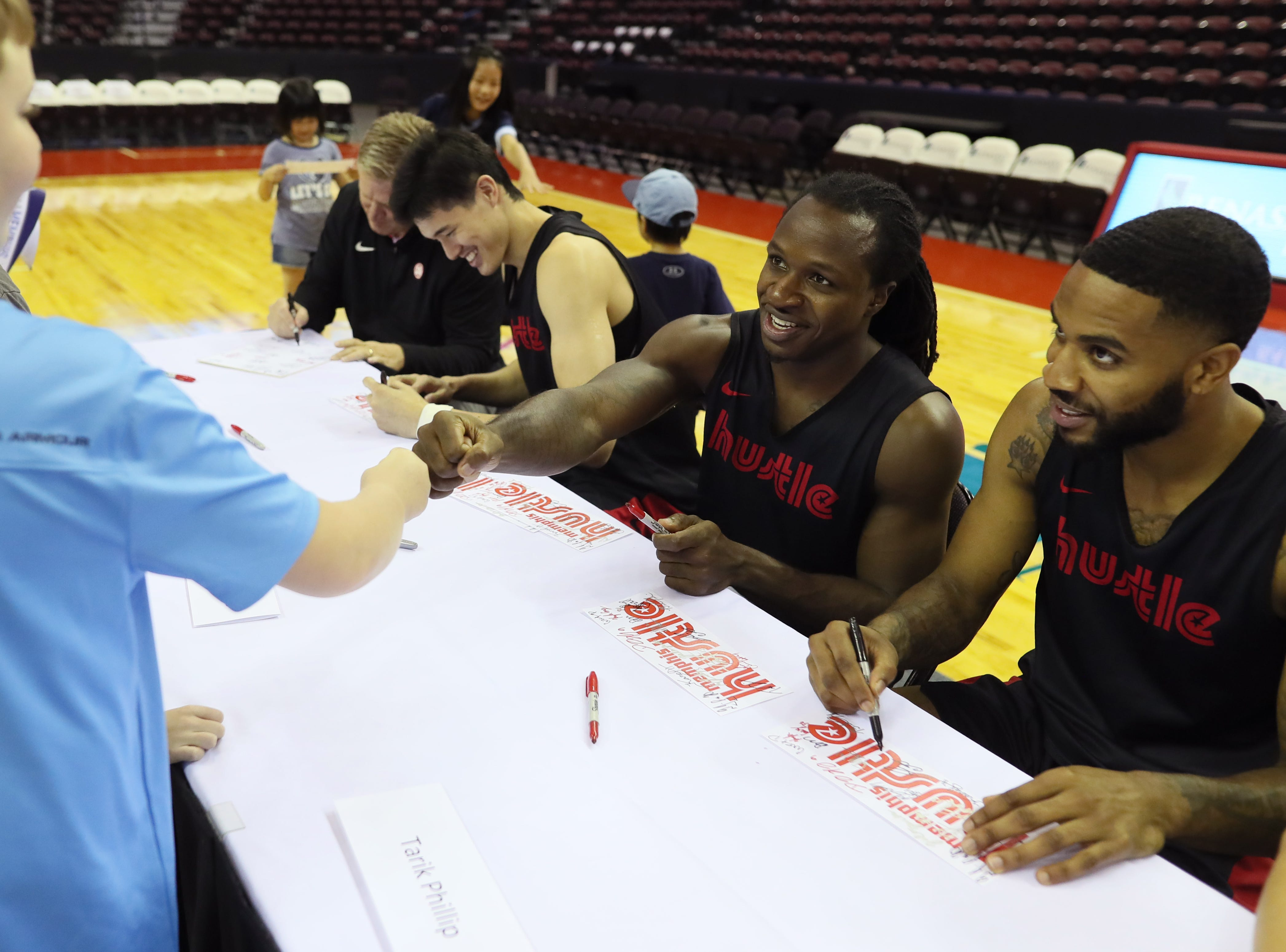 Memphis Hustle players Jay-R Strowbridge, center, and Tarik Phillip sign autographs for fans as they host Family Fun Day at the Landers Center on Sunday, Oct. 28, 2018.