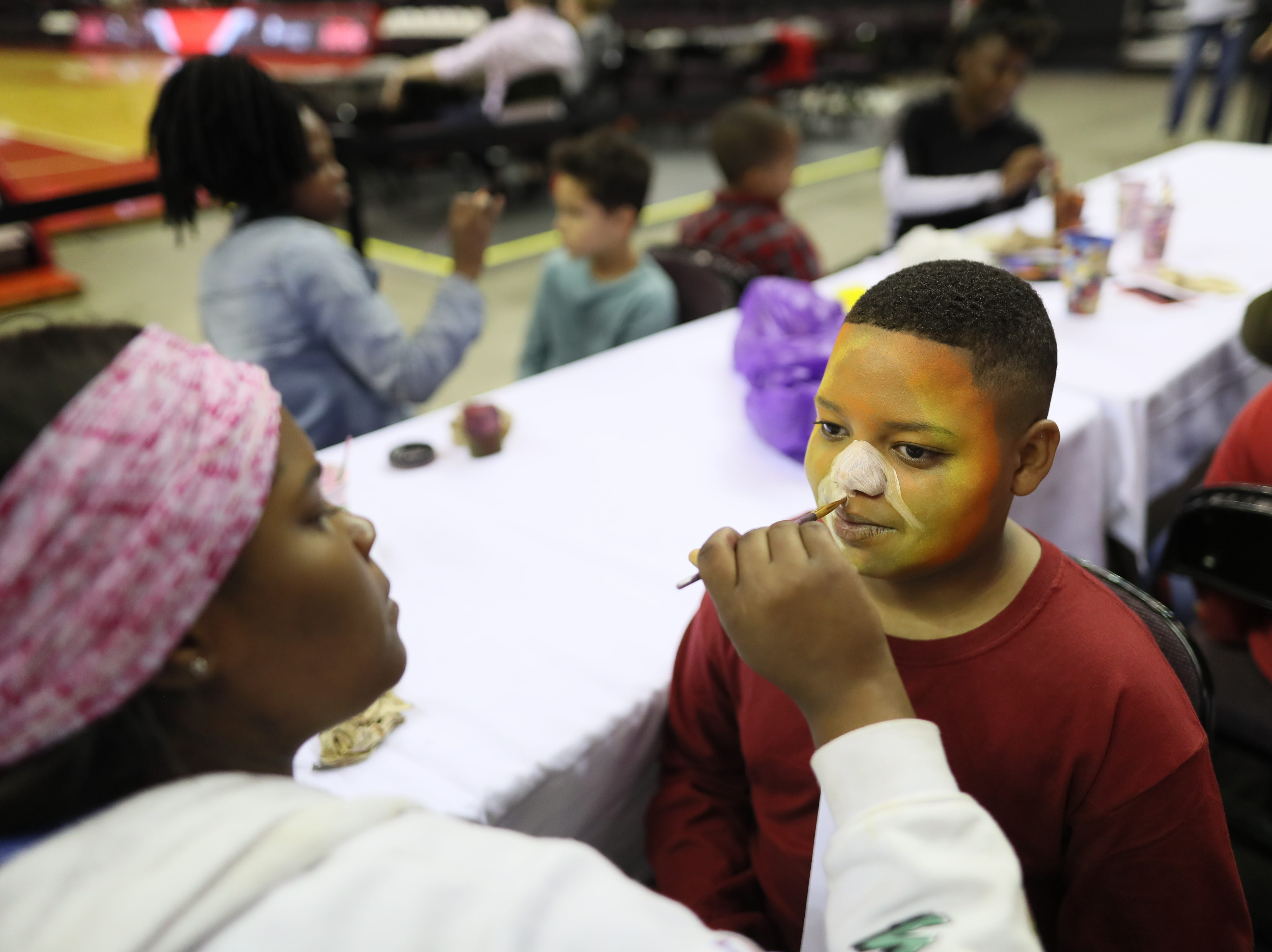 Antwain Forrest, 12, has his face painted by Shanyla Hunter, 17, during the Memphis Hustle Family Fun Day at the Landers Center on Sunday, Oct. 28, 2018.