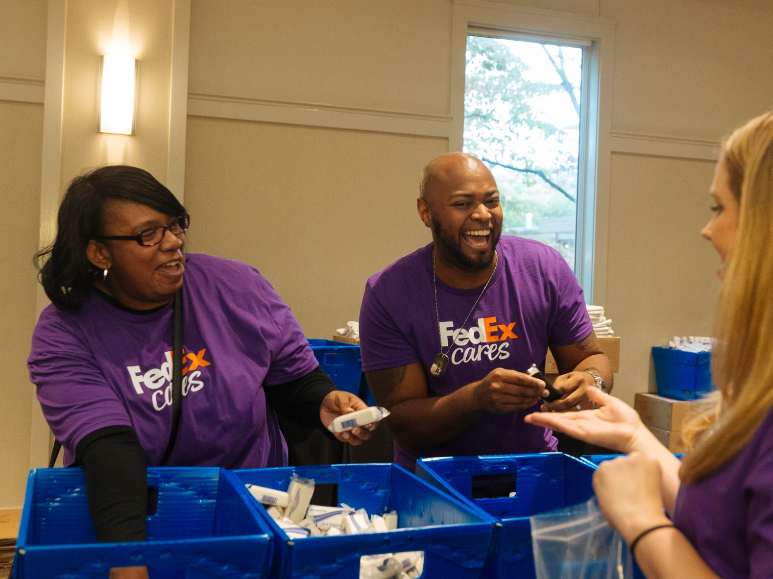 Lacie Wade and Jerome Heard sing along with fellow FedEx volunteers while assembling hygiene kits at the Memphis Botanic Gardens for Hurricanes Florence and Michael relief.