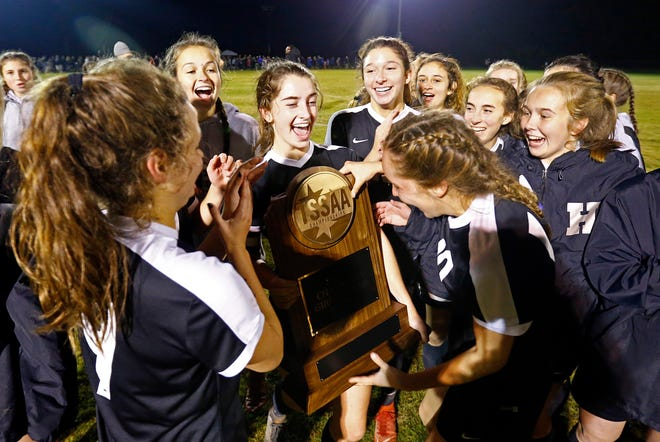 Houston's Kate Handel holds the trophy as she and her teammates celebrate after defeating Collierville in their Class AAA soccer championship match Saturday, Oct. 27, 2018, in Murfreesboro, Tenn.