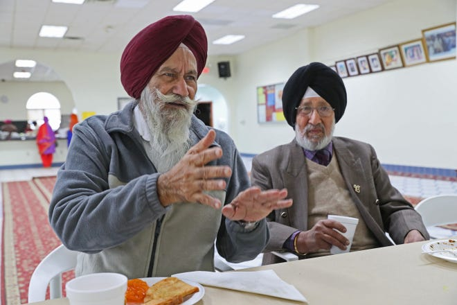 Harbans Singh (left) describes Sunday what he witnessed being in the Sikh Temple of Wisconsin in Oak Creek during a mass shooting Aug. 5, 2012. Fellow temple member Mohan Singh listens at right. They reacted with sorrow to news of the shooting Saturday at the Tree of Life Synagogue in Pittsburgh.