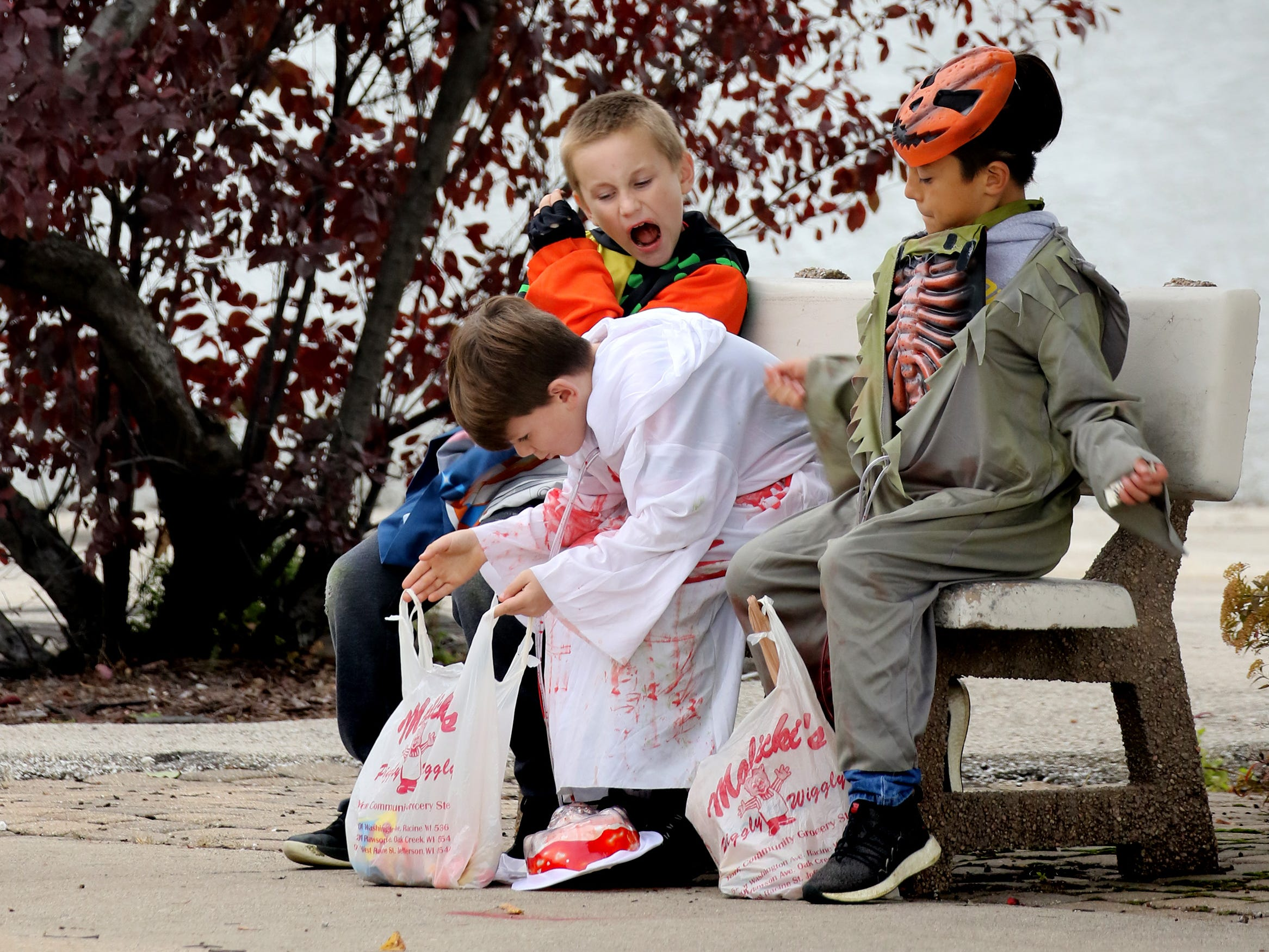 Children stop to check what they collected during the South Milwaukee Downtown Trick or Treating on Oct. 27.