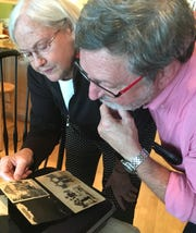 Janet Bode shows her brother John Schlosser a photo album of pictures that their uncle Harold Reilly made while in training, or were sent to him while in France. Several years ago Bode uncovered the photo album and Harold's transcribed letters from training and France. Schlosser had never seen either item.