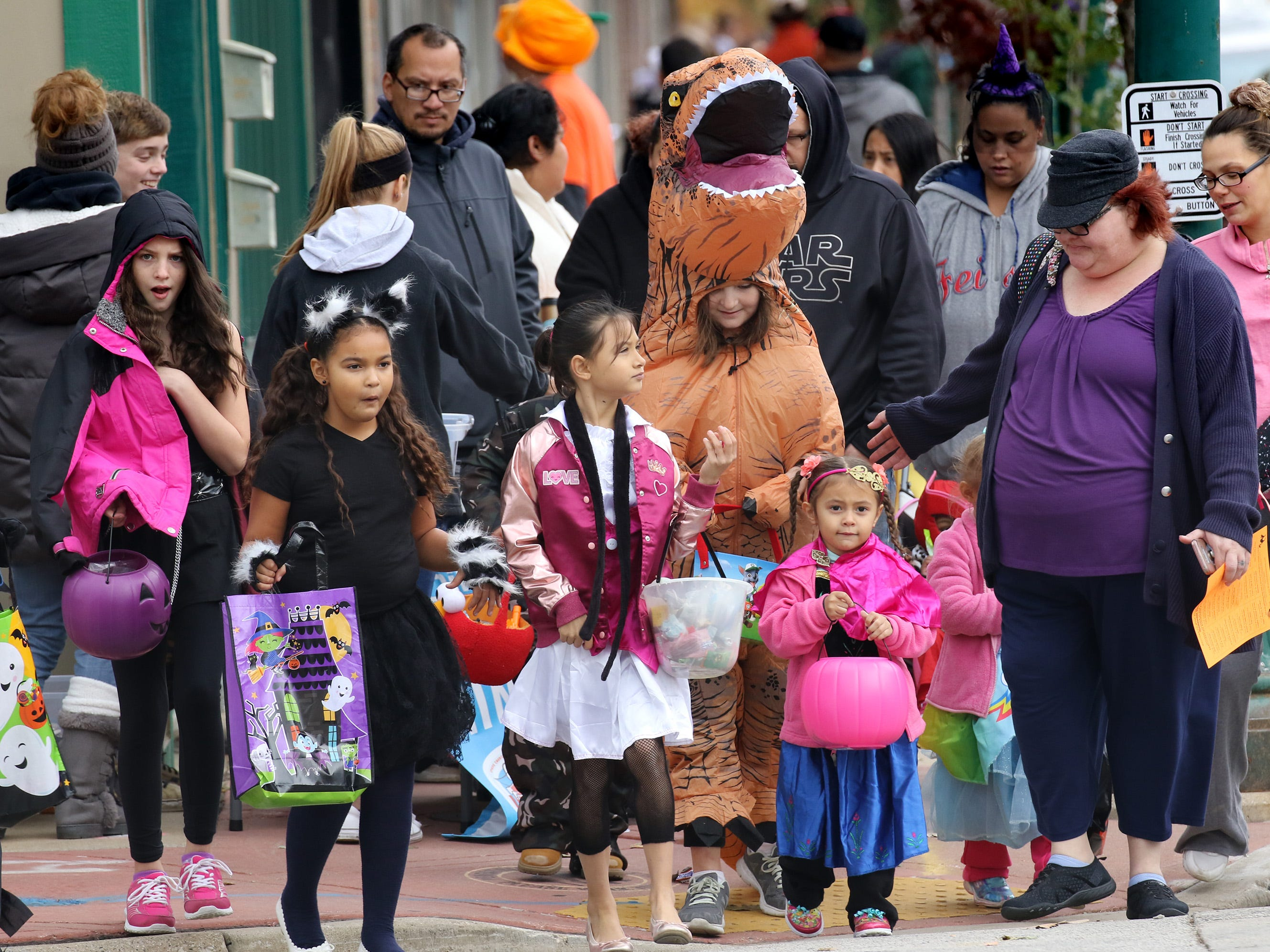 Trick or treaters wait to cross a side street along Greenfield Avenue during the West Allis Downtown Halloween Hunt on Oct. 27.