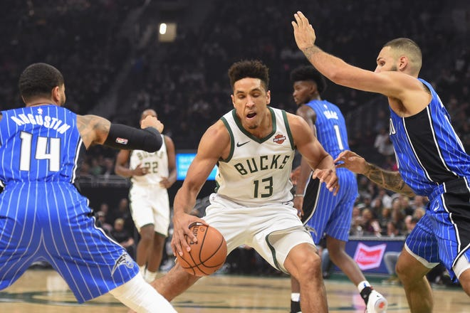 Bucks guard Malcolm Brogdon tries to split D.J. Augustin (left) and Evan Fournier of the Orlando Magic on a drive.