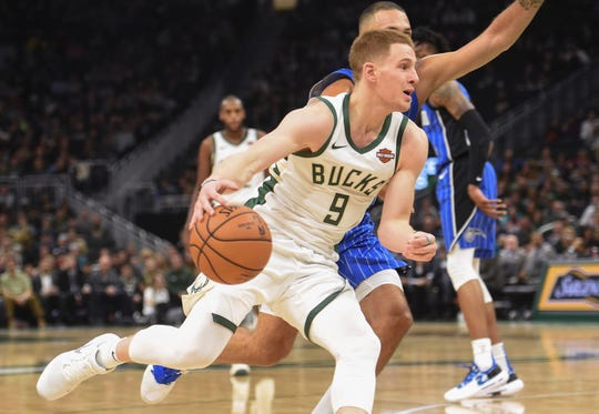 Bucks guard Donte DiVincenzo drives to the basket against Magic guard Evan Fournier. DiVincenzo hasn't played an NBA game since Jan. 1.
