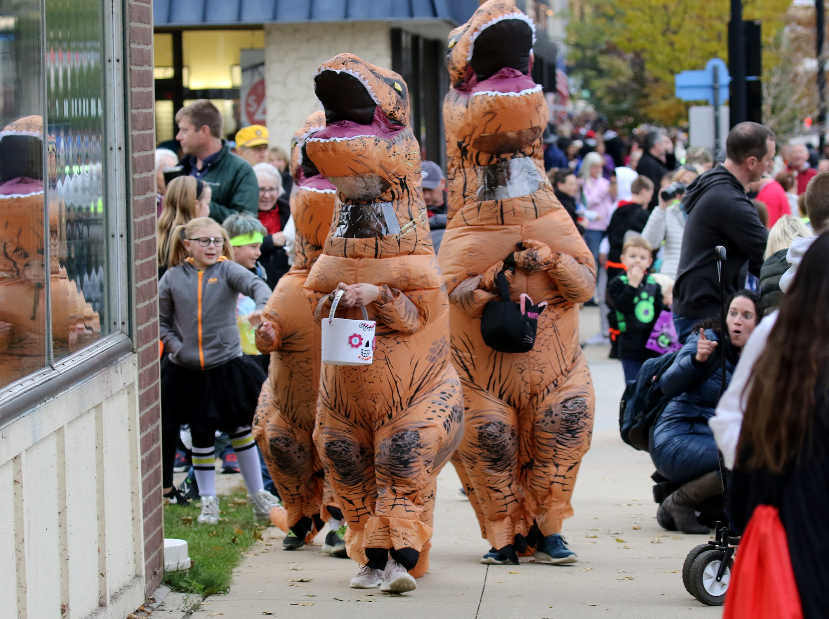 A trio of dinosaurs invade the downtown during the Oconomowoc Halloween Parade on Oct. 27 that followed several hours of Downtown Trick or Treating.