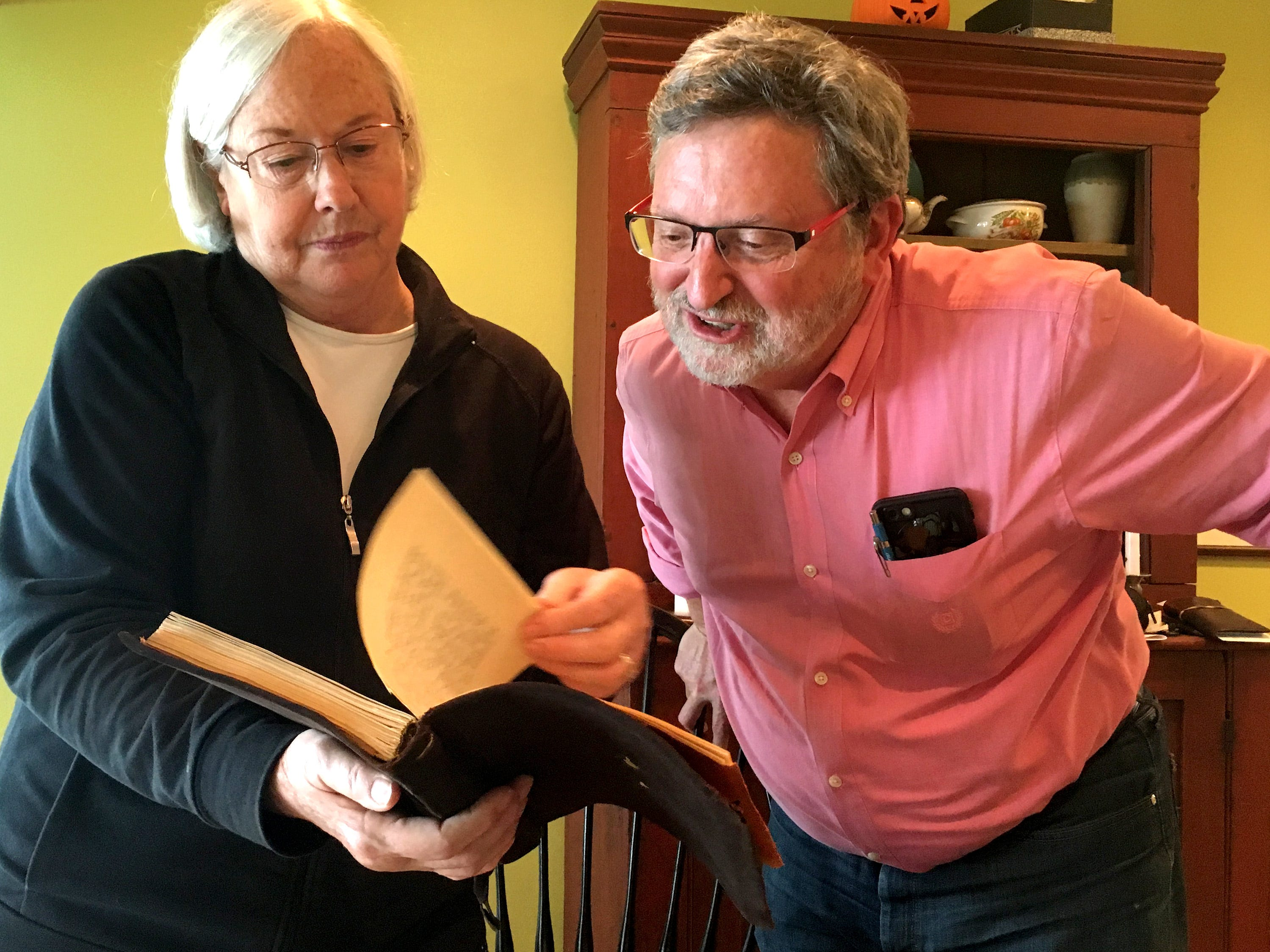 Janet Bode shows her brother John Schlosser a journal of their uncle Harold Reilly's transcribed letters from training and France that she uncovered with a photo album several years ago, neither of which Schlosser had ever seen before.