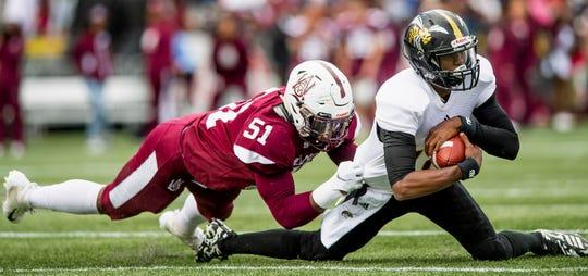 Alabama State University quarterback KHA'Darris Davis (12) is sacked by Alabama A&M outside linebacker Yurik Bethune (51) at Legion Field in Birmingham, Ala., during the Magic City Classic on Saturday October 27, 2018.