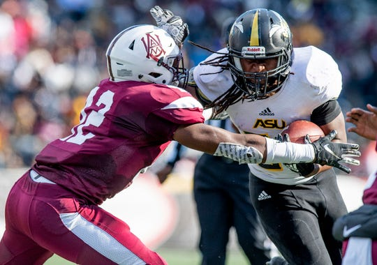 Alabama State University running back Tallesin Farmer (32)  is tackled by Alabama A&M cornerback Antoine Felton, Jr., (12) at Legion Field in Birmingham, Ala., during the Magic City Classic on Saturday October 27, 2018.