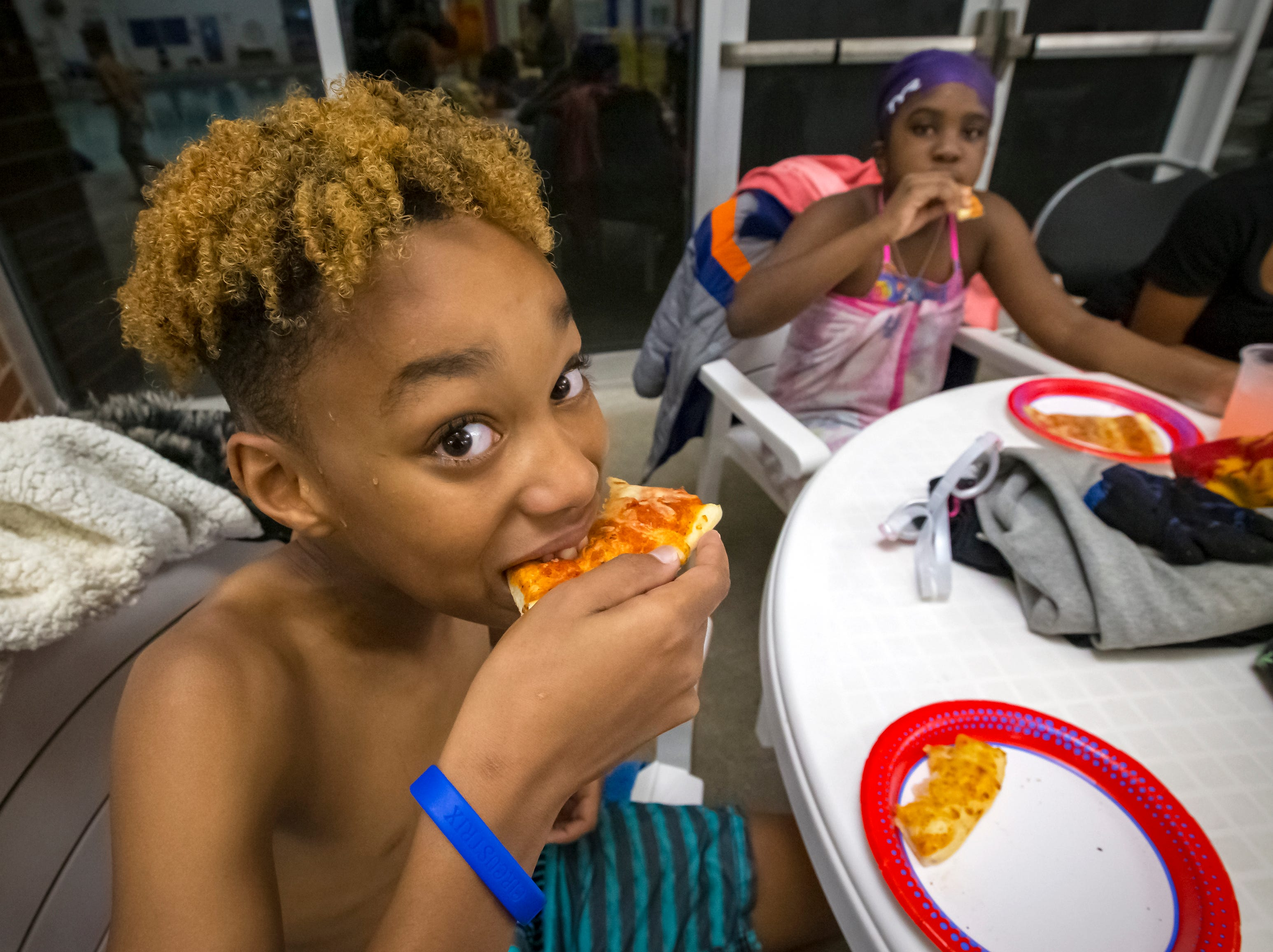 Kassam Bhegani eats a slice of pizza during the pizza party held at Murfreesboro Parks & Rec.'s Spooky Splash event at Patterson Park Community Center.