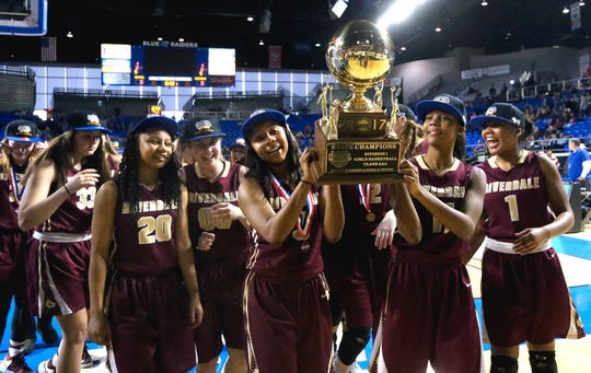 Riverdale's Anastasia Hayes (3) and her sister Aislynn Hayes (11) carry the championship trophy over to the Riverdale fans as the team celebrates its victory over Memphis Central in the Class AAA championship on March 11, 2017.