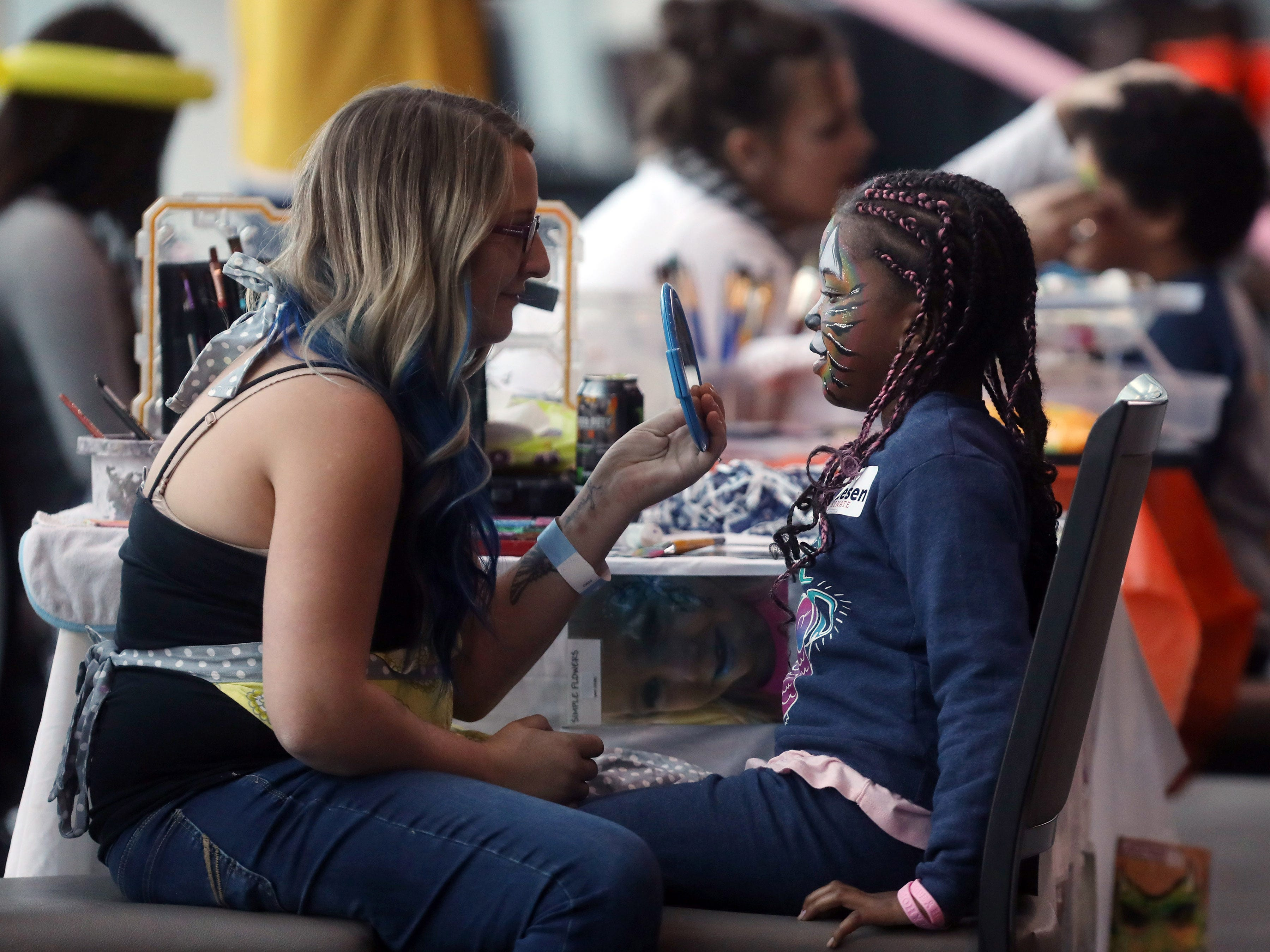 Tyler Taylor, right, admires the face painting she received from Grace Emison  Saturday, October 27, 2018, during a rally at Nissan Staidum for Phil Bredesen which celebrated his involvement in bringing the Titans and Predators to Nashville.