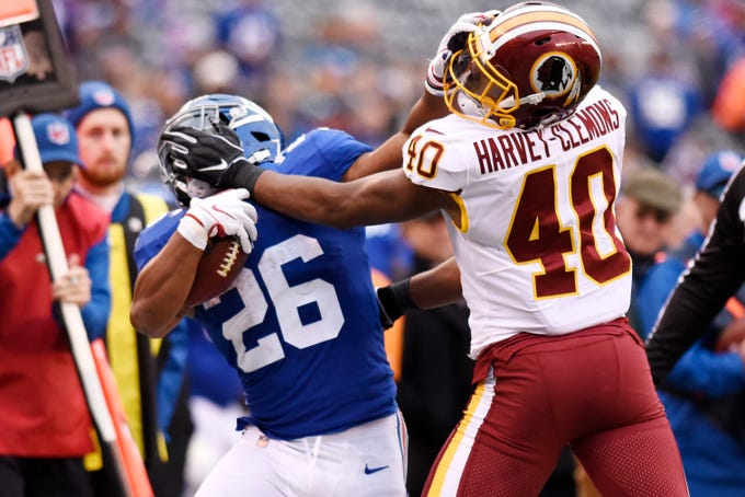 New York Giants running back Saquon Barkley (26) and Washington Redskins linebacker Josh Harvey-Clemons (40) stiff-arm each other in the second half. The Giants lose to the Redskins 20-13 on Sunday, Oct. 28, 2018, in East Rutherford.
