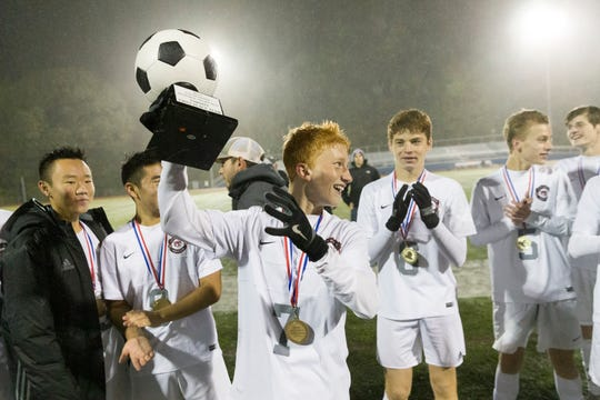 OAKLAND, NJ 10/27/2018  Glen Rock's Ben Zakowski (7) raises the trophy after his team's 3-0 victory over Ramsey in Saturday night's Bergen County Boys High School Soccer Tournament final.