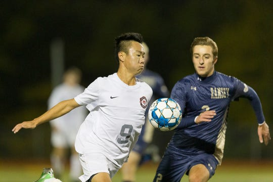 OAKLAND, NJ 10/27/2018  Glen Rock's Josh Kim (9) advances the ball past Ramsey's Charlie Illes in Saturday night's Bergen County Boys High School Soccer Tournament final.  Glen Rock soared to a 3-0 victory to take the trophy.