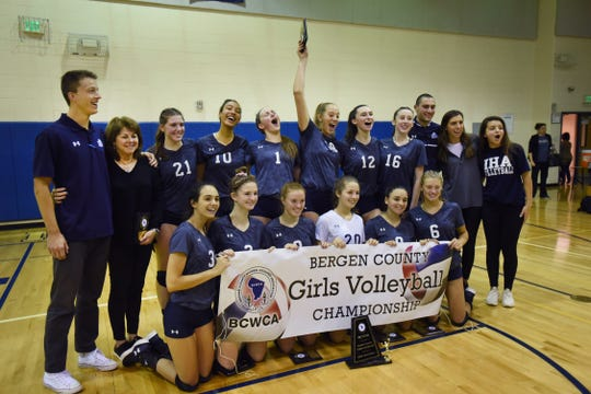 IHA team members and their coaches have a group picture taken after their win against Old Tappan during the 44th Bergen County girls volleyball tournament at NV/Old Tappan High School on 10/28/18. IHA won the championship 25 - 19, 25 -23.